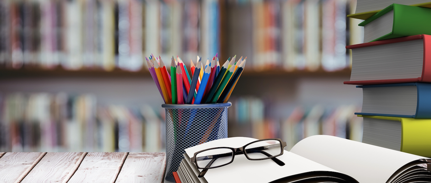 digital composite of school materials on table with library background